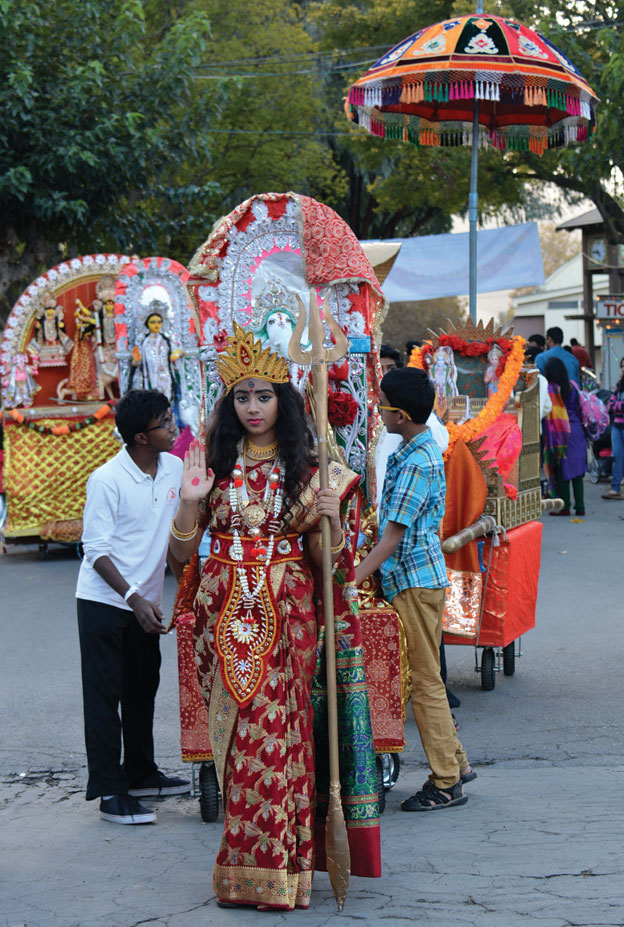 (Above): Kids and teens at the parade of deities, getting a glimpse of Hindu traditions. [Photo: Amar D. Gupta | Siliconeer]
