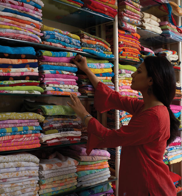 A woman shopping the traditional way, at a brick and mortar store in India.