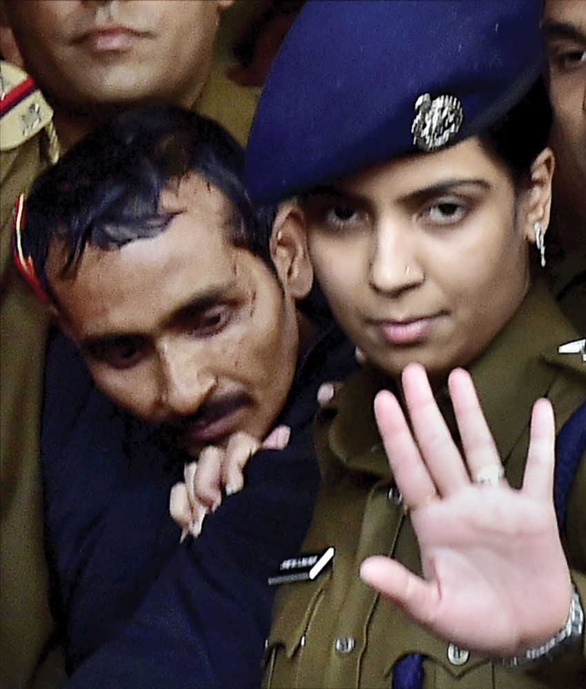 Police take away rape-accused Uber cab driver Shiv Kumar Yadav after he was produced before a Magistrate Court in New Delhi. Police arrested Yadav in Mathura on Dec. 7 for allegedly raping a 25-year-old female executive in Delhi. (Kamal Kishore | PTI)