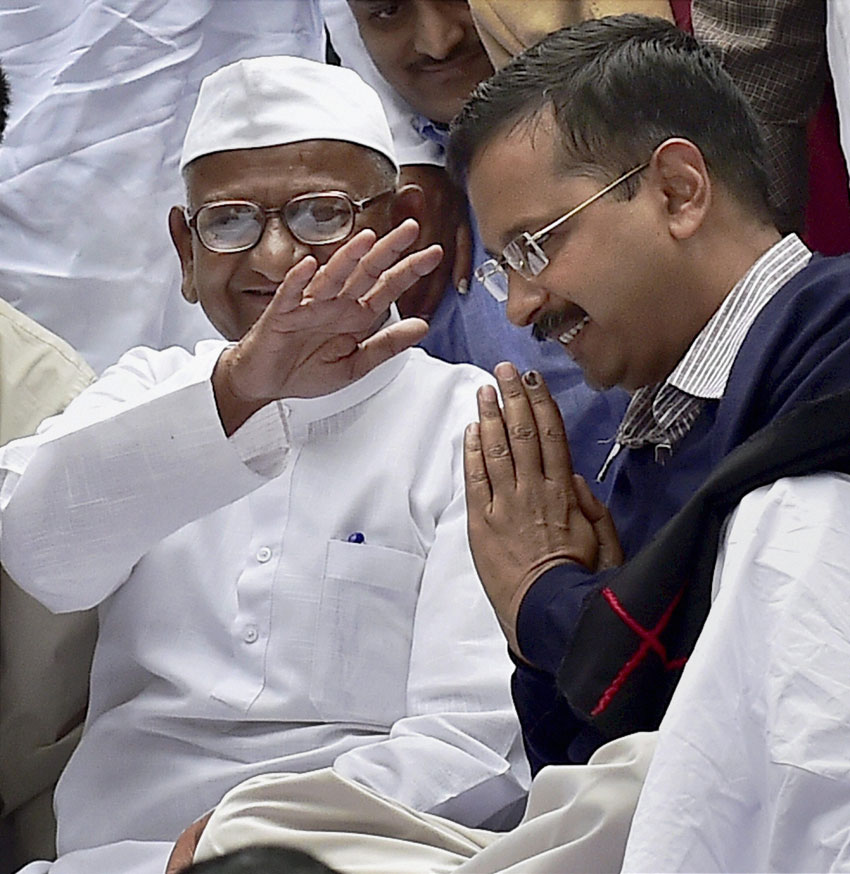 Delhi Chief Minister Arvind Kejriwal seeks blessings of social activist Anna Hazare as he shares stage with Anna on his two-day agitation against the ordinance on Land Acquisition Bill at Jantar Mantar in New Delhi, Feb. 24. (Kamal Kishore | PTI)