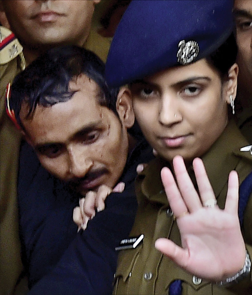 File photo of Police taking away rape accused cab driver Shiv Kumar Yadav after he was produced before a Magistrate Court in New Delhi. Police arrested Yadav in Mathura on Dec. 7 for allegedly raping a 25-year-old female executive in Delhi. The victim has recently sued Uber in a U.S. Court. (Kamal Kishore | PTI)