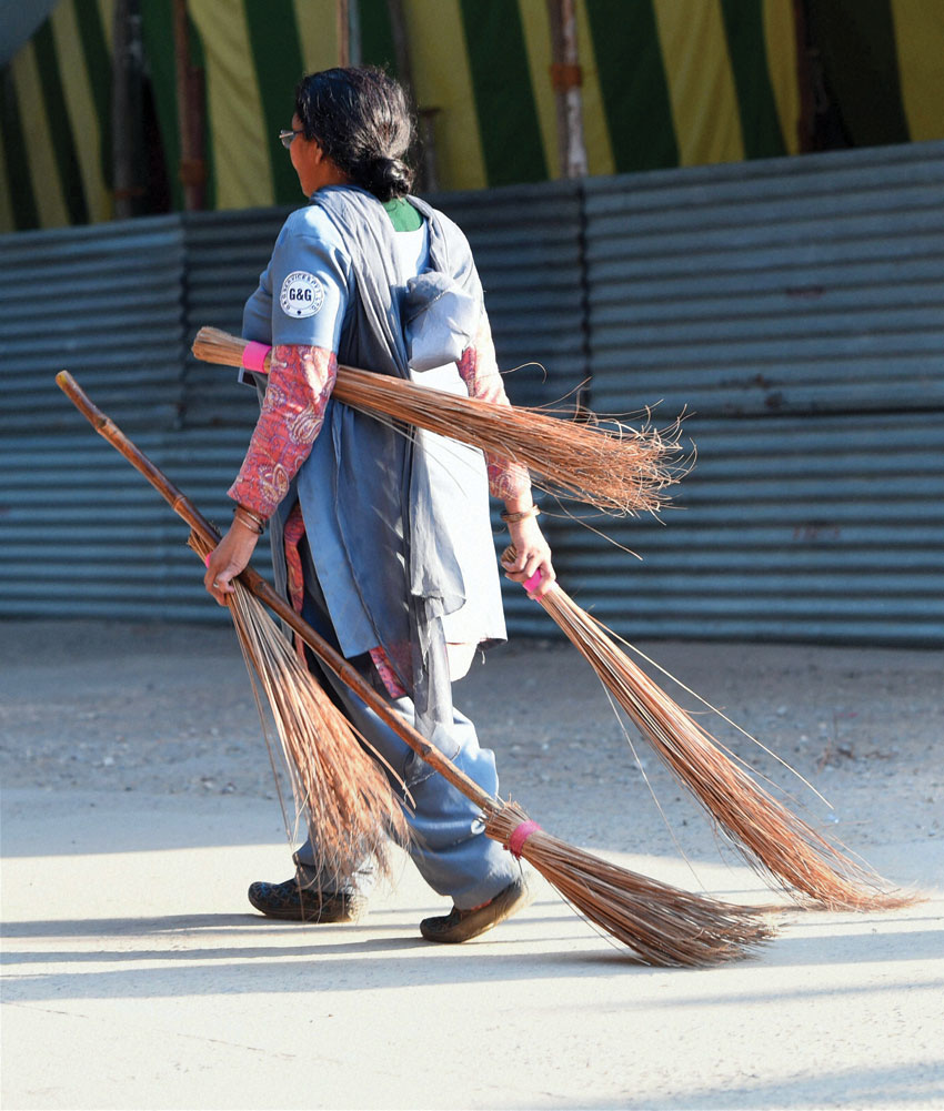 A woman carrying brooms at a poll counting center in New Delhi, Feb. 10. (Shahbaz Khan | PTI)