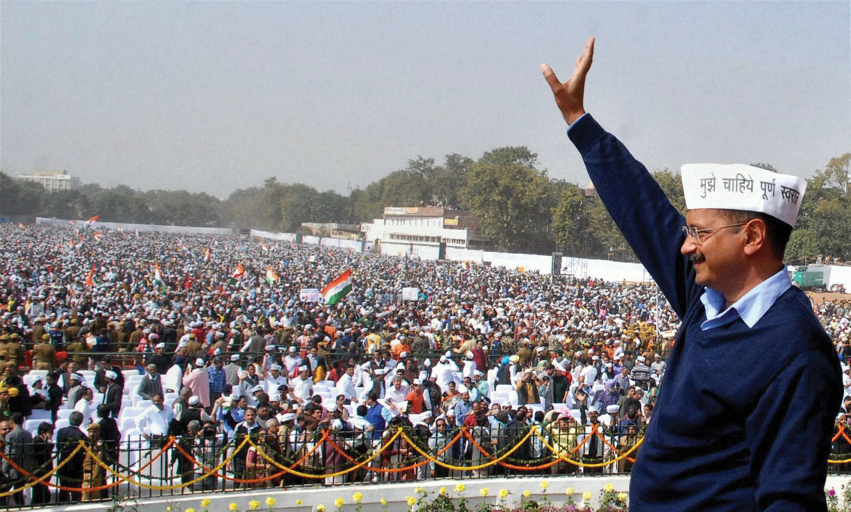 Delhi Chief Minister Arvind Kejriwal waves at supporters during the swearing-in ceremony at Ramlila Maidan in New Delhi, Feb. 14. (Press Trust of India)