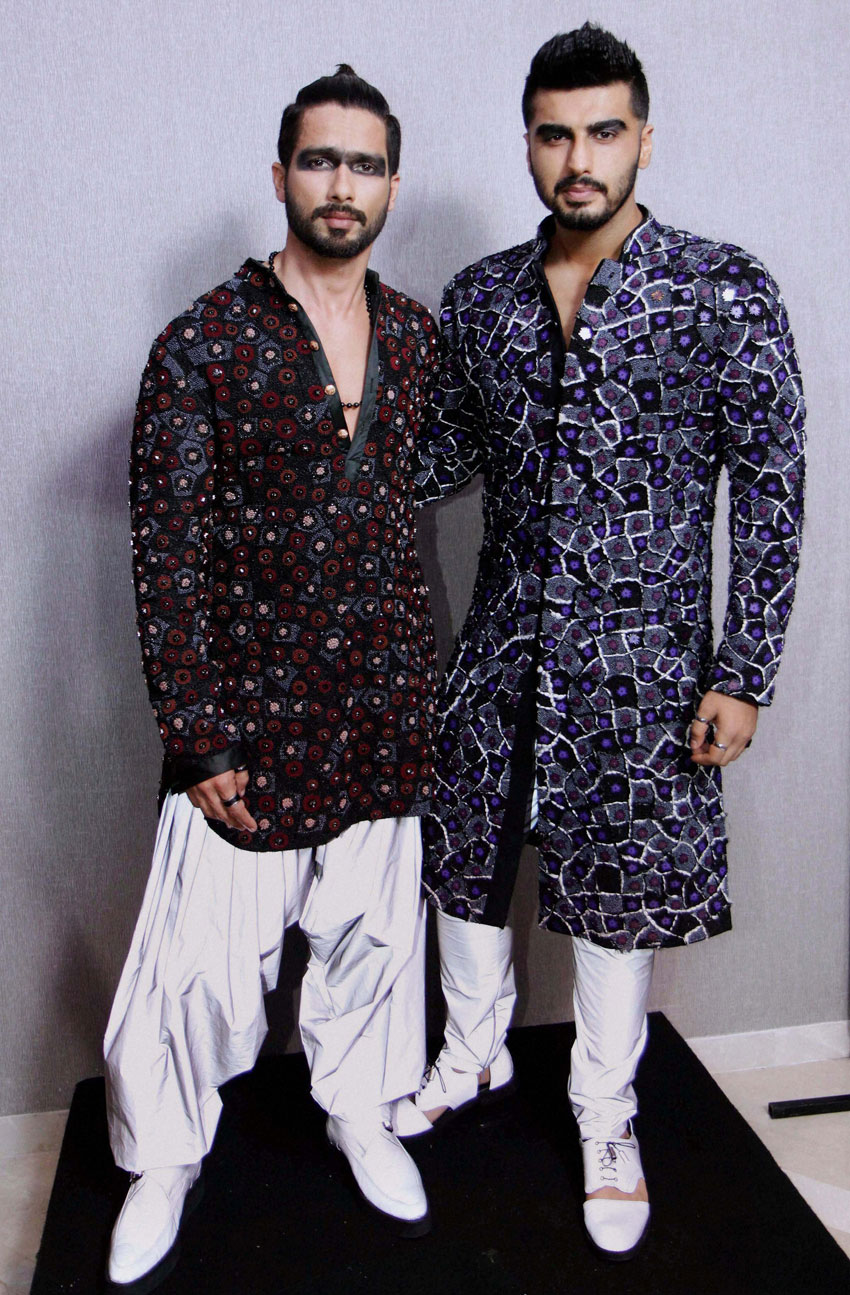 Bollywood actors Shahid Kapoor and Arjun Kapoor pose in an outfit by fashion designer Kunal Rawal, at the Lakme´ Fashion Week Summer Resort 2015, in Mumbai. (Press Trust of India)