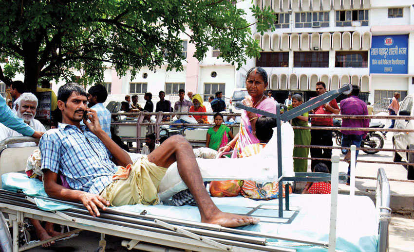 A patient lying outside a hospital, informing relatives over phone as panic grips Lucknow after tremors were felt from the 7.9 quake that hit Nepal. (Press Trust of India)