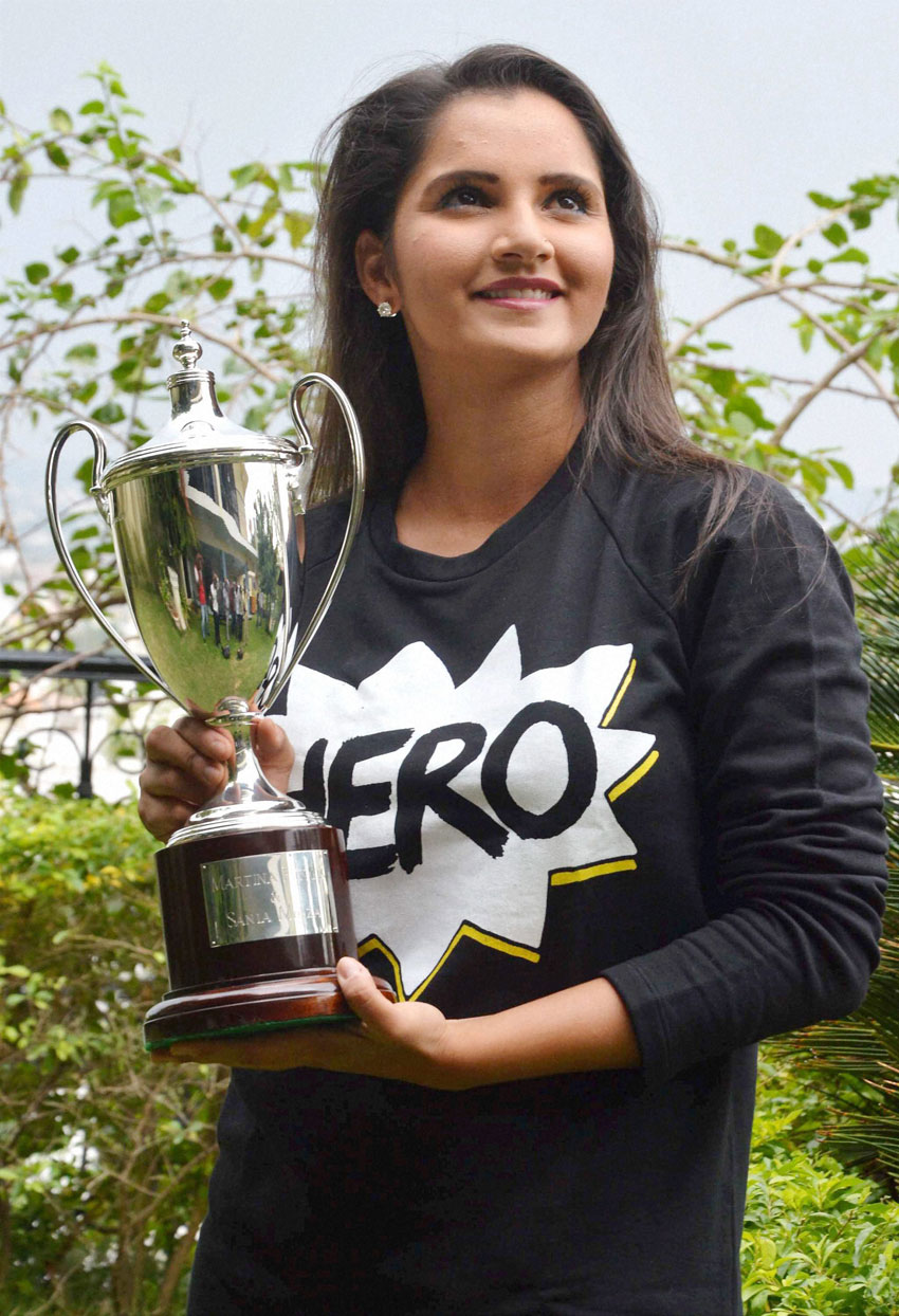 Sania Mirza poses for photographs with the Wimbledon Doubles trophy that she won recently, at a news conference at her residence, in Hyderabad, July 14. (Press Trust of India)