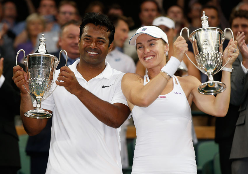 Leander Paes of India (l) and Martina Hingis of Switzerland hold the trophies after winning the mixed doubles final against Alexander Peya of Austria and Timea Babos of Hungary at the All England Lawn Tennis Championships in Wimbledon, London, July 12. (Alastair Grant | AP)