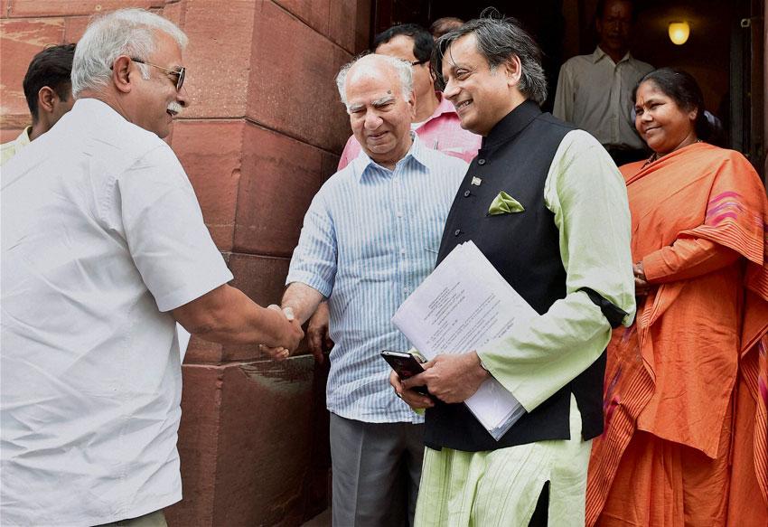 Indian Civil Aviation Minister Pusapati Ashok Gajapati Raju shakes hands with BJP MP Shanta Kumar as Congress leader Shashi Tharoor and Minister of State Sadhvi Niranjan Jyoti look on, at the Monsoon Session of Parliament House in New Delhi, July 24. (Kamal Kishore | PTI)