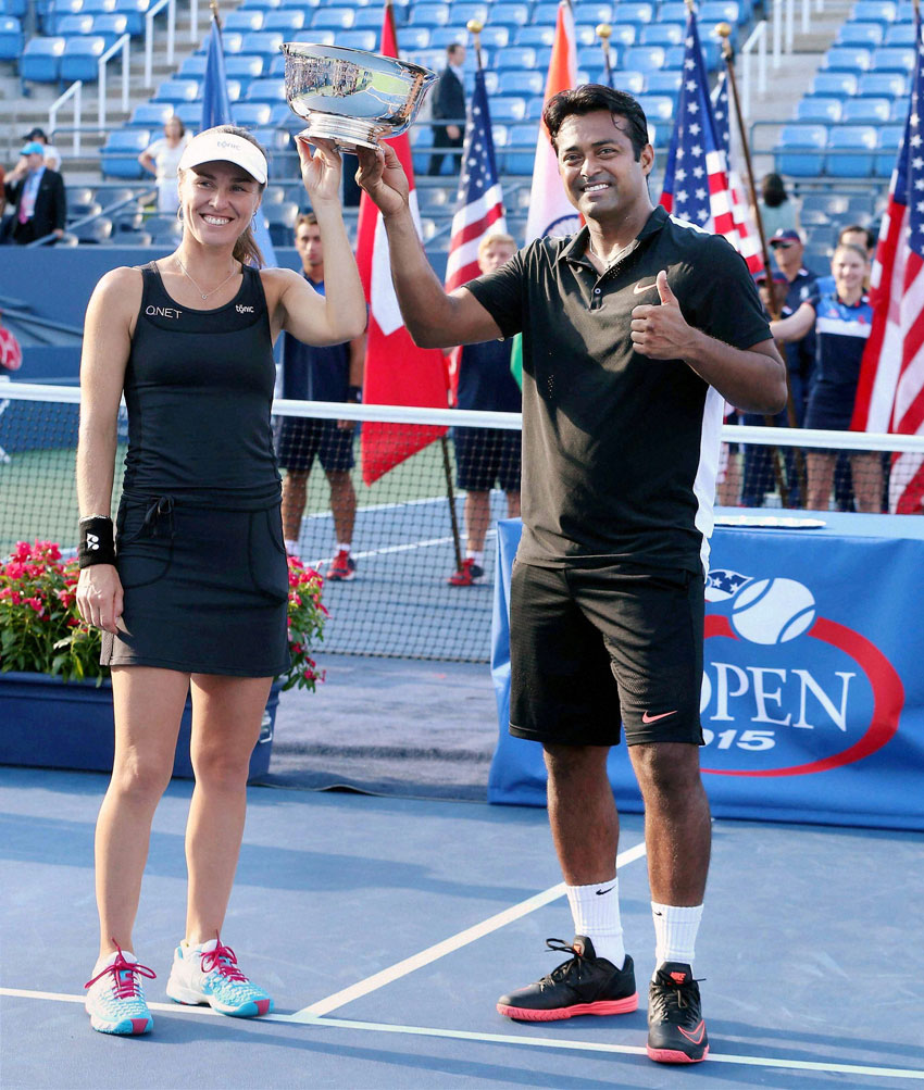 Leander Paes and Martina Hingis pose with the trophy after winning the mixed doubles final match against B Mattek-Sands and Sam Querrey at U.S. Open in New York, Sept. 11. (Press Trust of India)