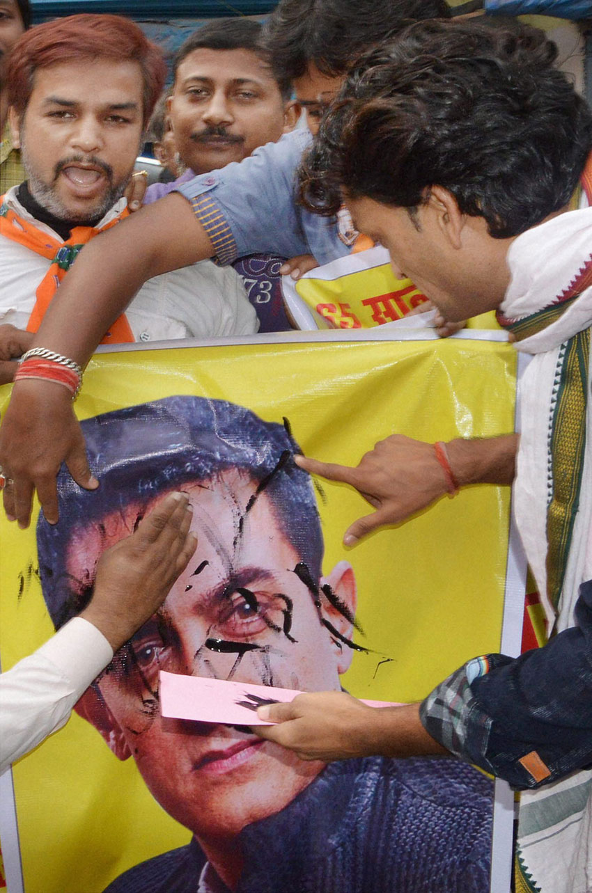 BJP workers smearing black ink on a poster of Aamir Khan in Patna, Nov. 24. (Press Trust of India)