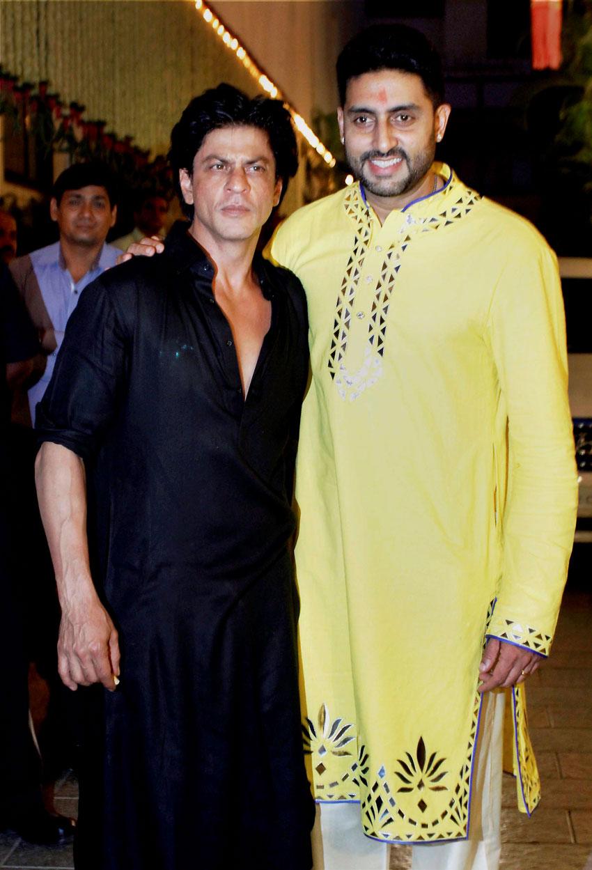 Abhishek Bachchan welcomes Shah Rukh Khan (l) at a Diwali party at his residence in Mumbai, Nov. 11. (Press Trust of India)