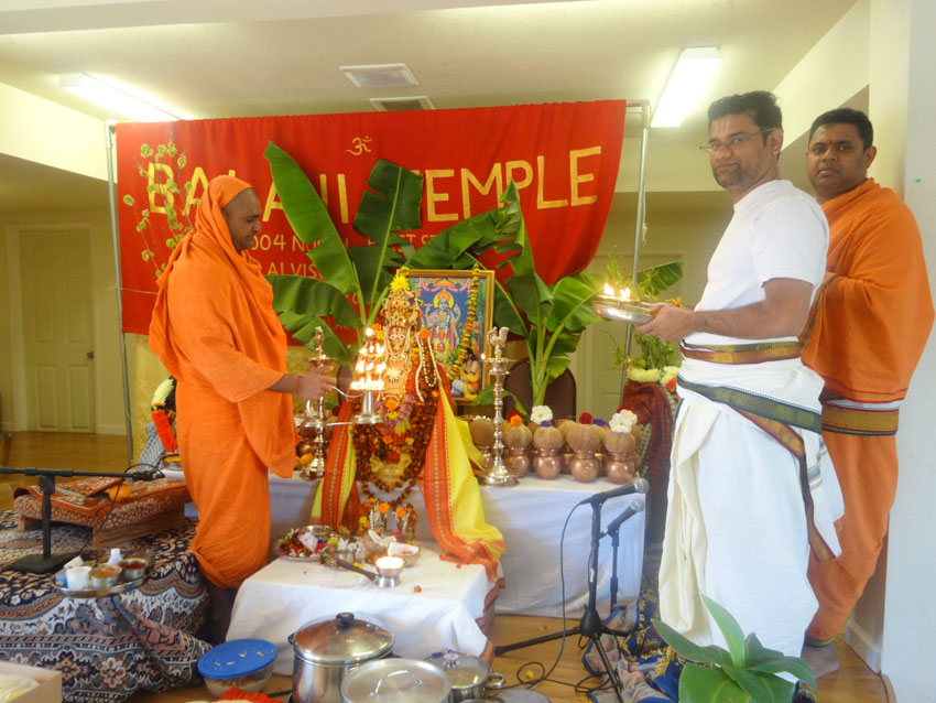 "Swami Narayananda performing ""aarti"" with priests."