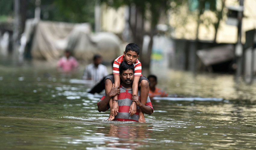 People carry children on their shoulders as they wade through flood waters in rain-hit Chennai, Dec. 3. (Press Trust of India)