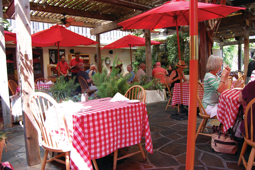 The Swiss Hotel's outdoors dining is Old Italy under a lattice dripping with vivid colorful flora. (Al Auger)