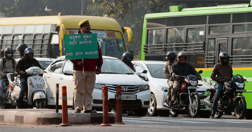 A Civil Defense volunteer holding a placard at ITO as Odd-Even scheme restricting movement of private cars, is operational in New Delhi, Jan. 2. (Shahbaz Khan | PTI)