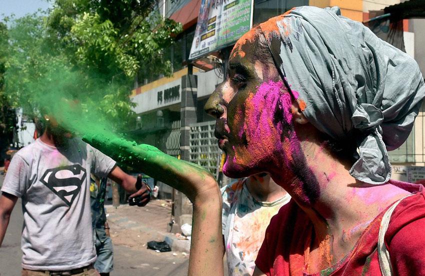 A foreign tourist sprays color while celebrating 'Holi' in Kolkata, Mar. 23. (Swapan Mahapatra   PTI)