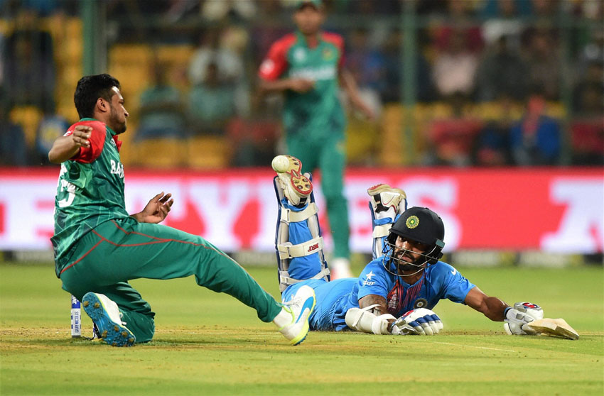 India's Shikhar Dhawan dives to reach the crease during the World T20 match against Bangladesh at Chinnaswamy Stadium in Bengaluru, Mar. 23. (Shailendra Bhojak | PTI)