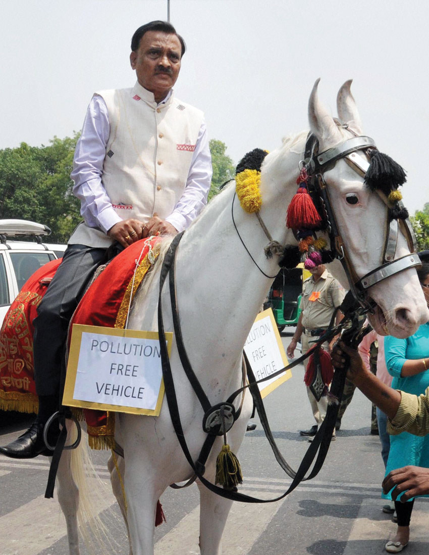 BJP MP Ram Prasad Sharma rides a horse on his way to attend Parliament session in New Delhi, April 27, marking a protest against the odd-even scheme implemented by the AAP-led government in Delhi. (Press Trust of India)