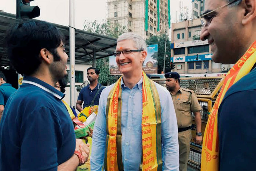 Apple CEO Tim Cook interacts with Anant Ambani, son of industrialist Mukesh Ambani, outside Siddhivinayak Temple in Mumbai, May 18. Apple India head Sanjay Kaul is also seen. (Press Trust of India)