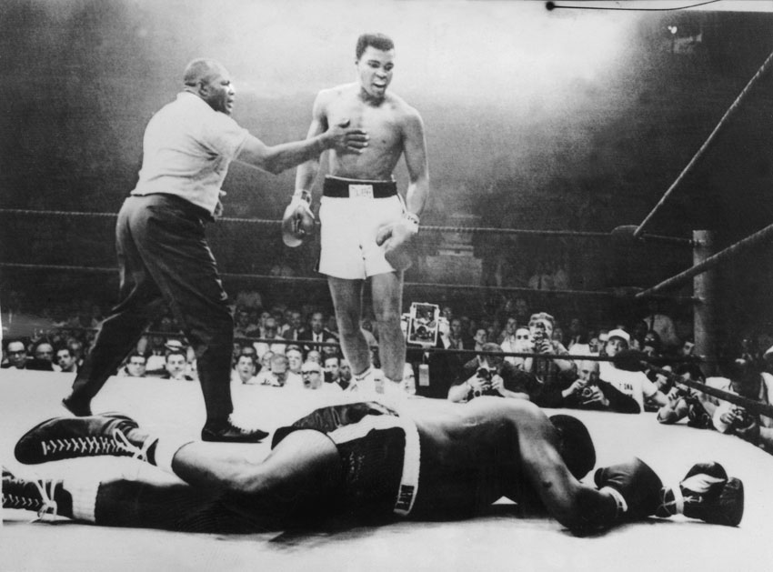 In this photo taken on May 26, 1965, in Lewiston, during the world championship heavyweight boxing in which the boxer Muhammad Ali (Cassius Clay) (c) retained his title as world champion by defeating Sonny Liston (ground) by first round knockout after one minute of a fight refereed by Joe Walcott. (AFP | Getty Images)