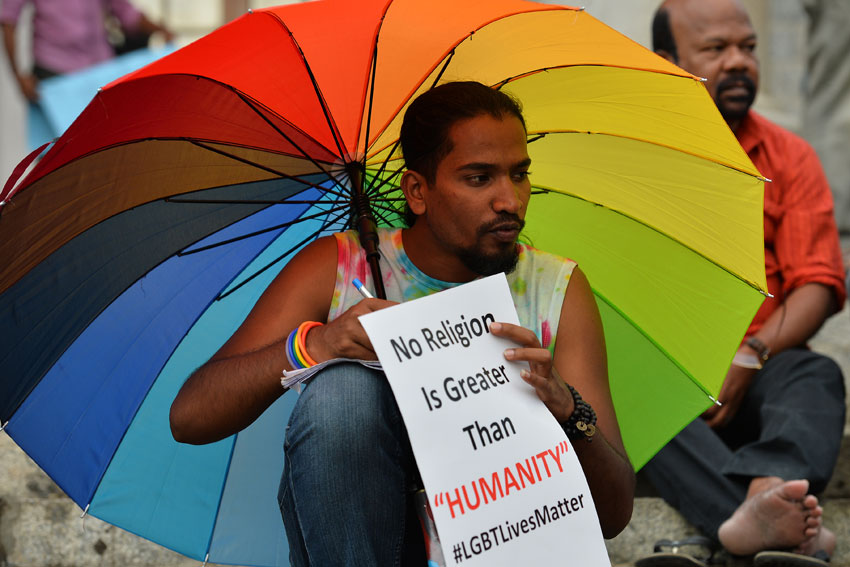 An Indian LGBT activist holds a placard during a demonstration and candlelight vigil held in Bangalore, June 14, condemning the killing of 49 people in an attack on a gay nightclub in Orlando by a gunman. (Manjunath Kiran | AFP | Getty Images)