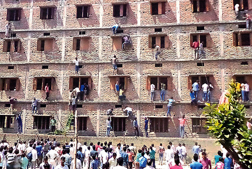 In this photograph taken on March 19, 2015, relatives of students taking school exams climb the walls of the exam building to help pass candidates answers to questions in Vaishali in the eastern state of Bihar. Authorities in eastern India were left red-faced on March 19, 2015, after images of relatives scaling the walls of a school exam center to pass notes to candidates were broadcast on local television. Dozens of people were shown clinging to the windows of one four-storey building in the eastern state of Bihar, where more than 1.4 million teenagers are sitting their school leaving exams. (AFP | Getty Images)