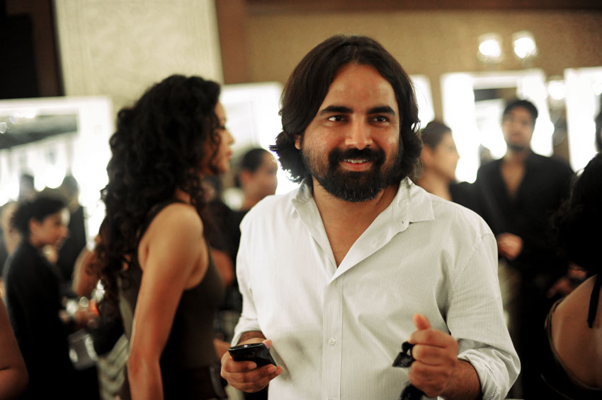 "In a picture taken on Aug. 12, 2012, Indian fashion designer Sabyasachi Mukherjee (c) smiles backstage before his fashion show in New Delhi. Mukherjee's efforts to modernize the ""sari,"" by using unusual fabrics like velvet while maintaining its iconic silhouette, has fueled a revival of the traditional drape. (Roberto Schmidt 