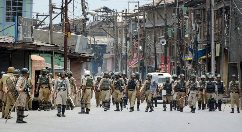 CRPF Personnel move towards their camp as curfew was lifted after 17 days, at Safa Kadal, a town in the Srinagar district, July 26. (Press Trust of India)