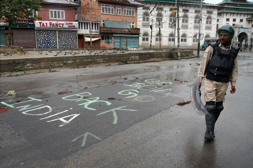 A security personnel stands guard near a graffiti as curfew was reimposed in parts of Kashmir, in Srinagar, July 27. (S. Irfan | PTI)