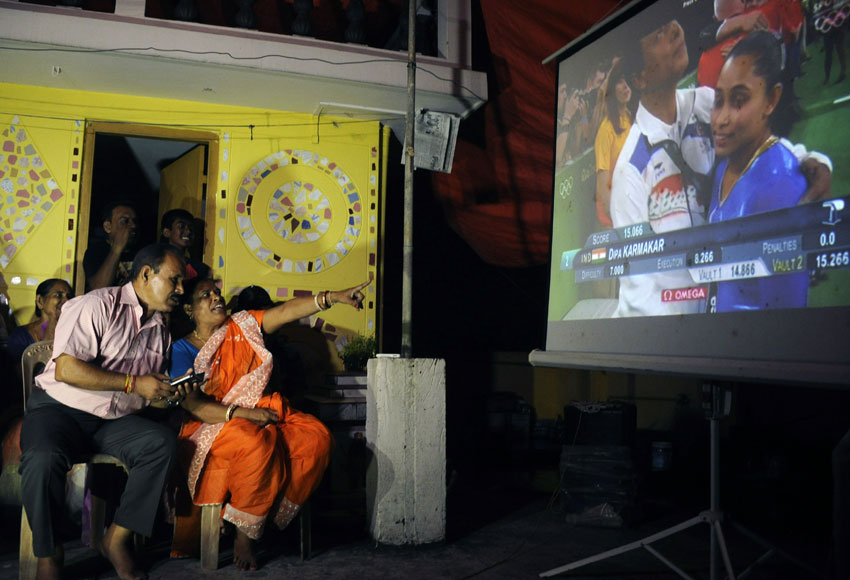 The parents of Indian gymnast Dipa Karmakar, Dulal Karmakar (l) and Gouri Karmakar (r) along with family members watch a projector screen in Agartala late Aug. 14, as it shows the performance of Dipa in the vault finals of the gymnastics event at the 2016 Rio Olympic Games. Dipa finished the event in fourth position with a score of 15.066 points. (AFP | Getty Images)