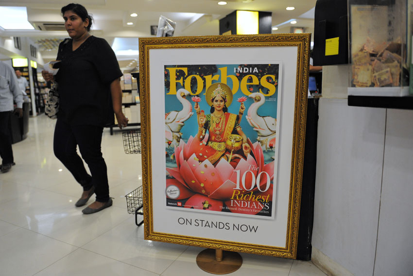 """File photo of a customer as she walks past a reproduction of the December 2012 issue of """"Forbes India"""" magazine, showing a depiction of Hindu Goddess Lakshmi on the cover, at a bookstore in Ahmedabad, Gujarat, Nov. 5, 2012. (Sam Panthaky/AFP/Getty Images)"""