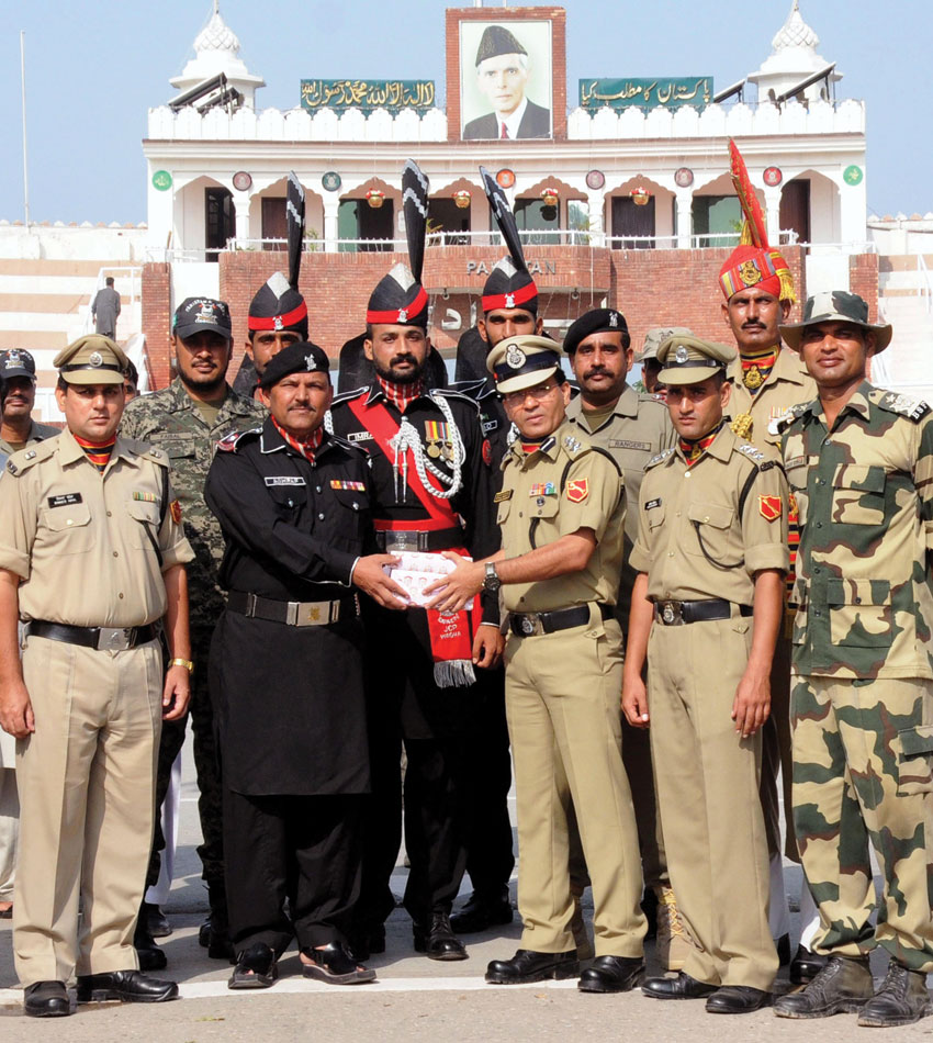 Border Security Force Commandant Sudeep, (r), offers a box of sweets to Pakistan Rangers Superintendent Ashraf, (l), on the occasion of India's Independence Day at the Attari-Wagah border, Aug. 15. (Press Trust of India)