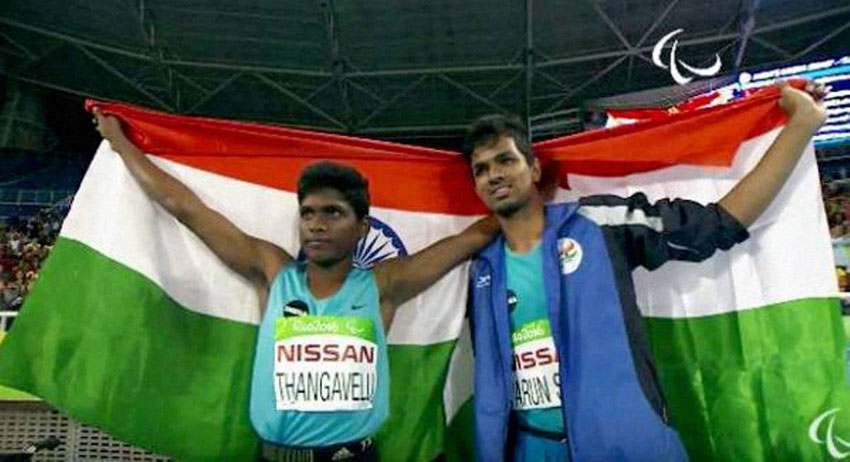 Paralympics participants Mariyappan Thangavelu (l) and Varun Singh Bhati walk with India's flag after winning gold and bronze medals respectively in the men's high jump event in Rio, Sept. 9. (Press Trust of India)