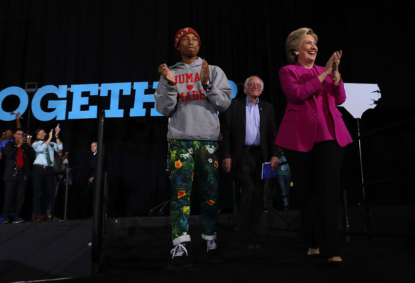 (L-r): Recording artist Pharrell Williams, U.S. Sen. Bernie Sanders (I-VT) and Democratic presidential nominee Hillary Clinton greet supporters during a campaign rally at Coastal Credit Union Music Park at Walnut Creek, Nov. 3, in Raleigh, North Carolina. (Justin Sullivan/Getty Images)