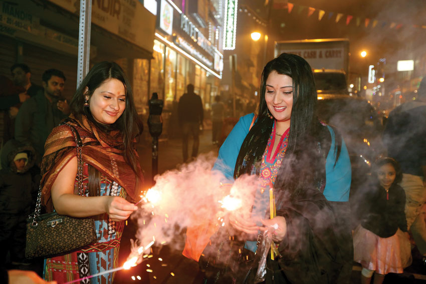 Indian American women burning firecrackers to mark Diwali in New Jersey, Oct. 31. No prior permission was taken for fireworks but the city police cooperated. (Press Trust of India)