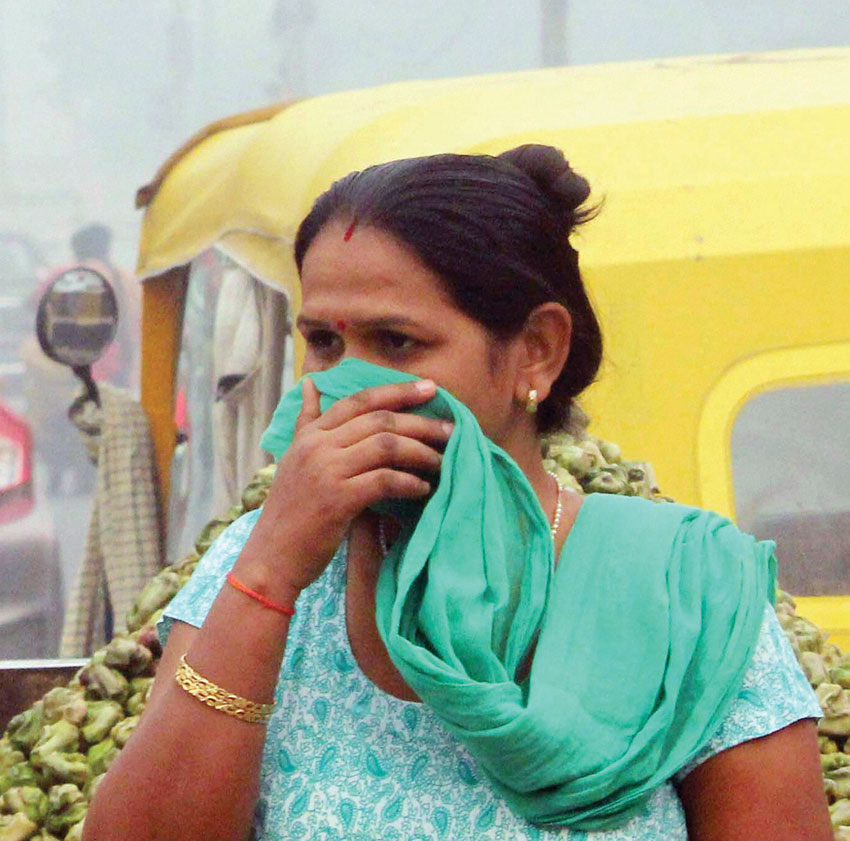 A woman covers her nose due to smog and air pollution in Gurgaon, Nov. 2. (Press Trust of India)