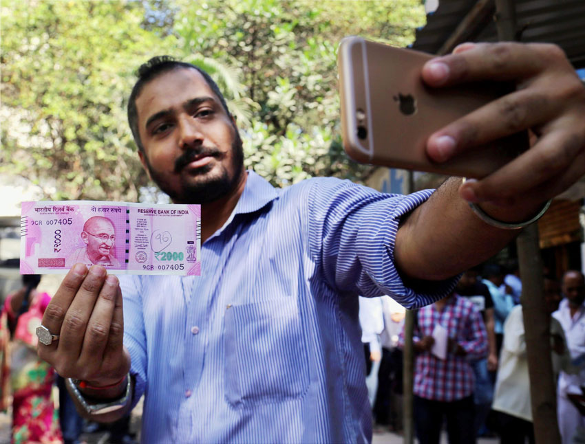 A man takes selfie with new Rs. 2,000 note in Thane, Mumbai, Nov. 10. (Press Trust of India)