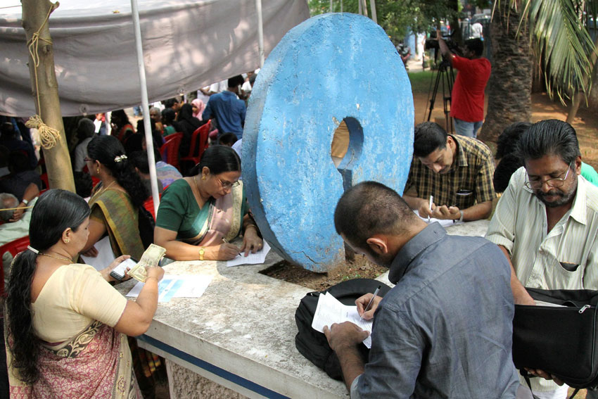 People fill forms outside a bank to get their old Rs. 500 and Rs. 1,000 notes exchanged in Kozhikode, Nov. 10. (Press Trust of India)