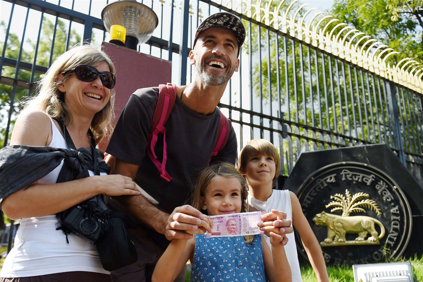 Tourists from Croatia show their new Rs. 2,000 note after they exchanged their old Rs. 500 and Rs. 1,000 notes at RBI Regional headquarters in Chennai, Nov. 10. (R. Senthil Kumar/PTI)