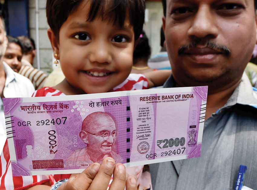 A child shows the new Rs. 2,000 note after exchanging old Rs. 500 and Rs. 1,000 notes in Chennai, Nov. 10. (Press Trust of India)