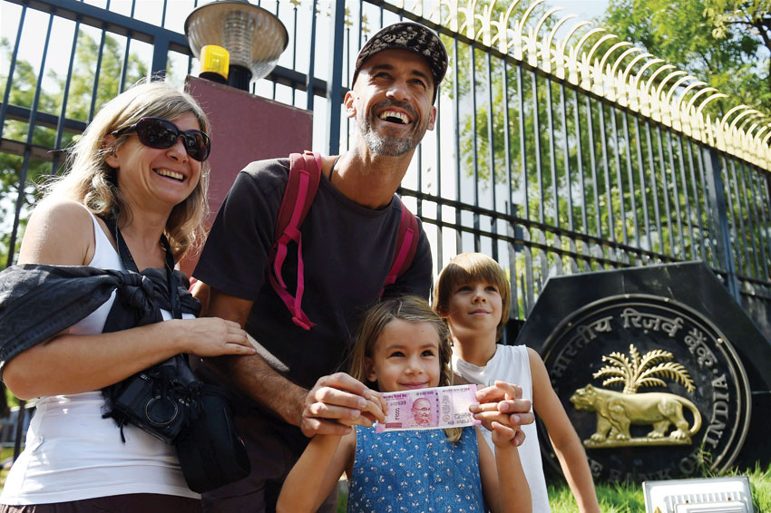 Tourists show their new Rs. 2,000 note after they exchanged their old Rs. 500 and Rs. 1,000 notes at RBI Regional headquarters in Chennai, Nov. 10. (R. Senthil Kumar/PTI)