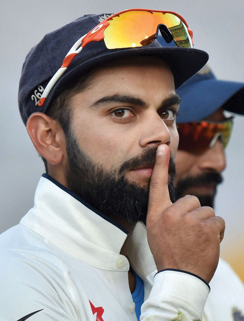 "Indian captain Virat Kohli gestures ""silent gesture"" towards Indian fans as he celebrates LBW decision against England's Ben Stokes during the 3rd day of 3rd India-England test match in Mohali, Nov. 28. Stokes had celebrated Virat Kohli's dismissal with a silent gesture earlier. (Vijay Verma/PTI)"