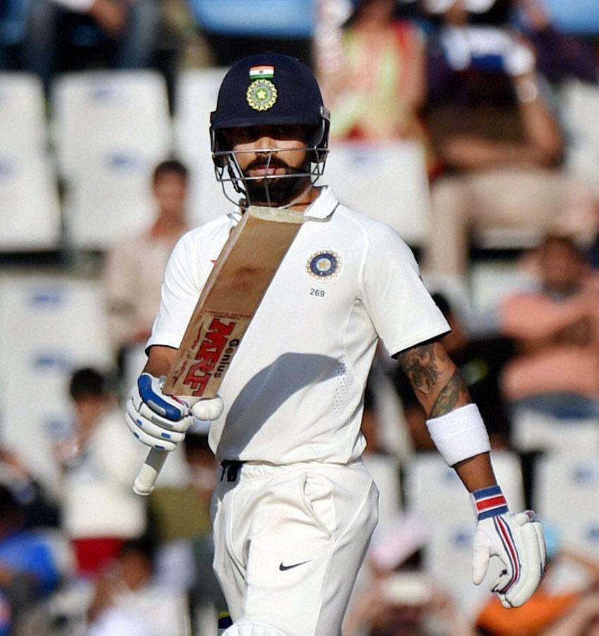 Indian skipper Virat Kohli celebrates his half century during the 2nd day of 3rd test match against England in Mohali, Nov. 27. (Vijay Verma/PTI)