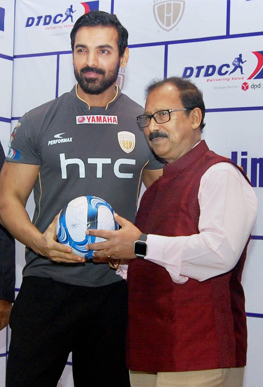 DTDC Chairman and Managing Director Subhasish Chakraborty presents a football to Bollywood actor and owner of North-East United Football Club (NEUFC) John Abraham during an event organized by DTDC in Guwahati, Nov. 30. (Press Trust of India)
